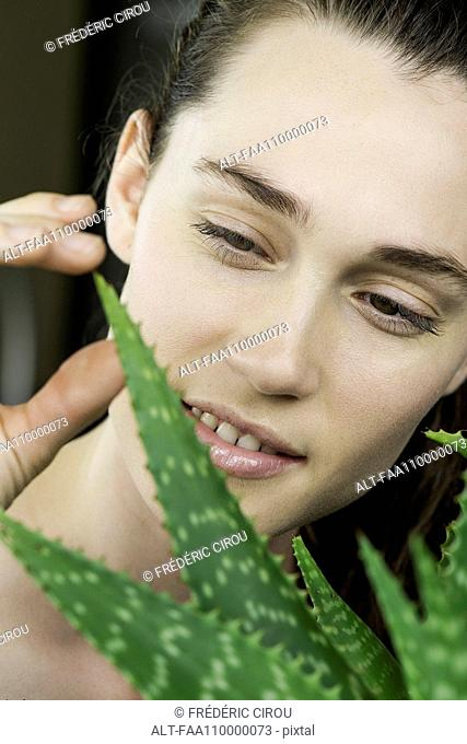 Young woman toucing aloe vera plant