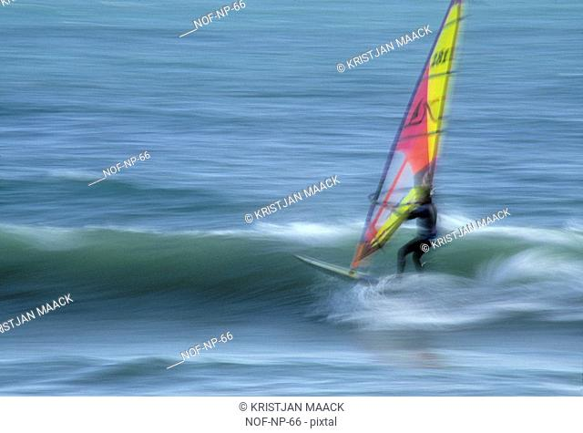 Windsurfer riding across a wave