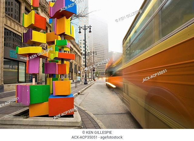 Traditional orange Winnipeg transit buses passing modern art on Portage Avenue. Winnipeg, Manitoba, Canada
