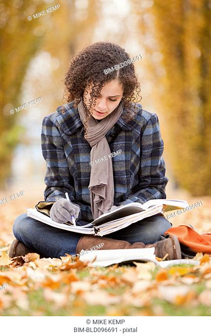 Caucasian woman doing home work in autumn leaves