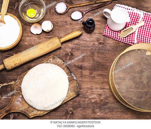 yeast dough made from white wheat flour and ingredients on a brown wooden table, top view