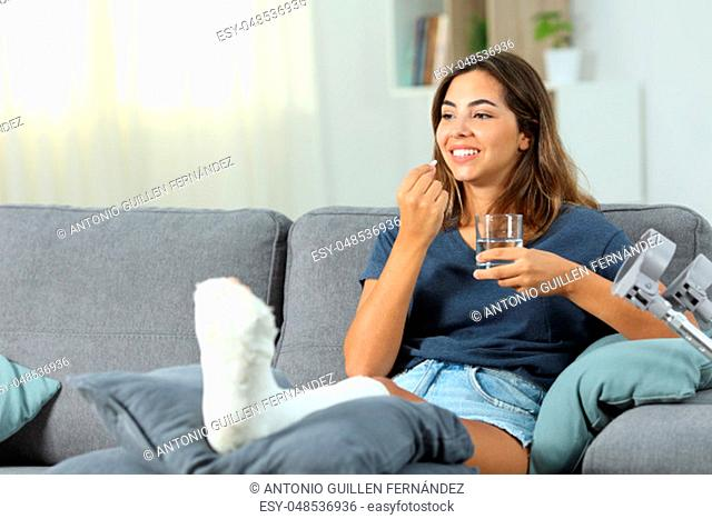 Happy disabled woman taking a painkiller pill sitting on a couch in the living room at home