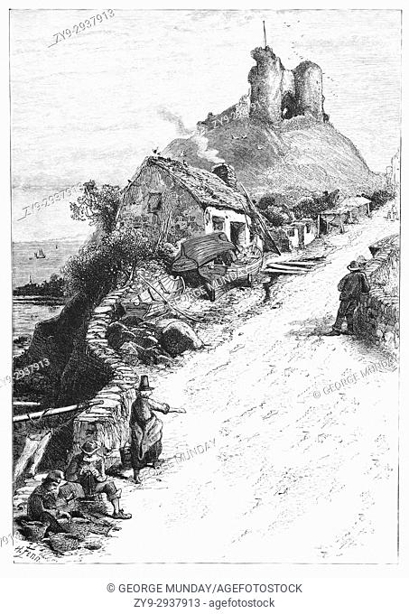 1870: A humble traditional thatched cottage, and locals, below Criccieth Castle situated on the headland overlooking Tremadog Bay