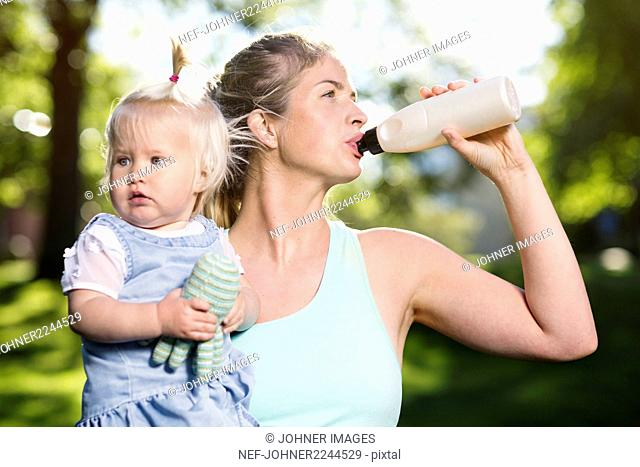 Woman with baby girl drinking water
