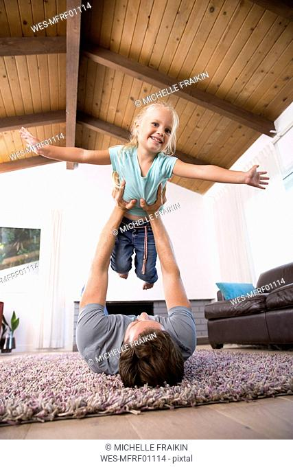 Father playing with daughter on carpet in living room at home