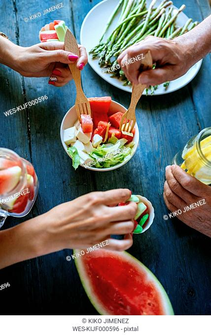 Close-up of hands eating salad, watermelon, lemonade, asparagus and candy