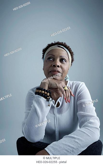 Portrait pensive African American mature woman wearing headscarf and beaded bracelet, looking away