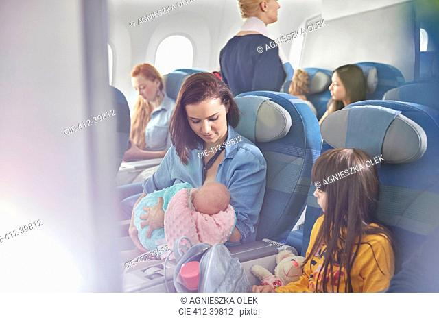 Mother holding baby on airplane