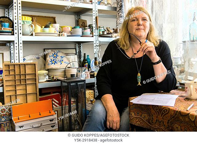Tilburg, Netherlands. Mature adult, caucasian woman maintaining her own shop in vintage household items and furniture
