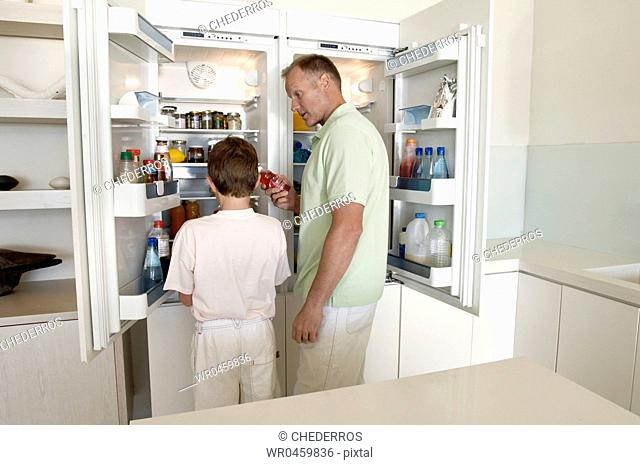 Side profile of a mature man standing with his son in front of an open refrigerator