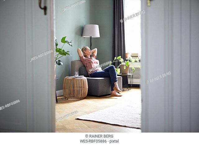 Relaxed mature woman sitting at home