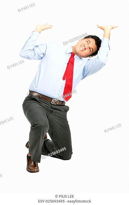 A stressed latino businessman in business clothes on knee using arms pushing up, resisting against crushing imaginary weight, object under heavy stress
