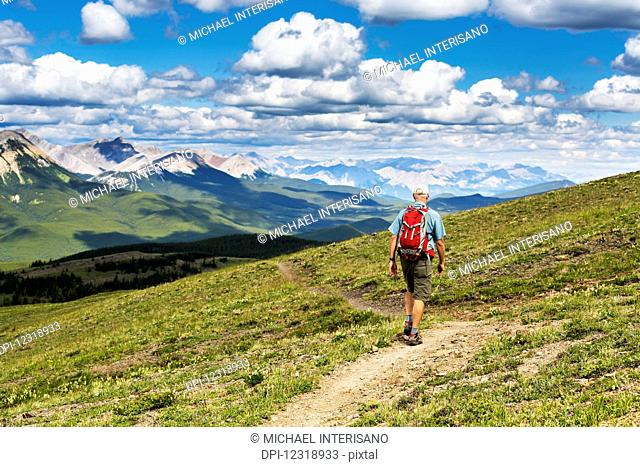 Male hiker walking along a hillside trail overlooking mountain range and valley with blue sky and cloud, West of Bragg Creek; Alberta, Canada