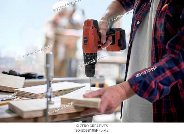 Cropped shot of female carpenter drilling wood in furniture making workshop