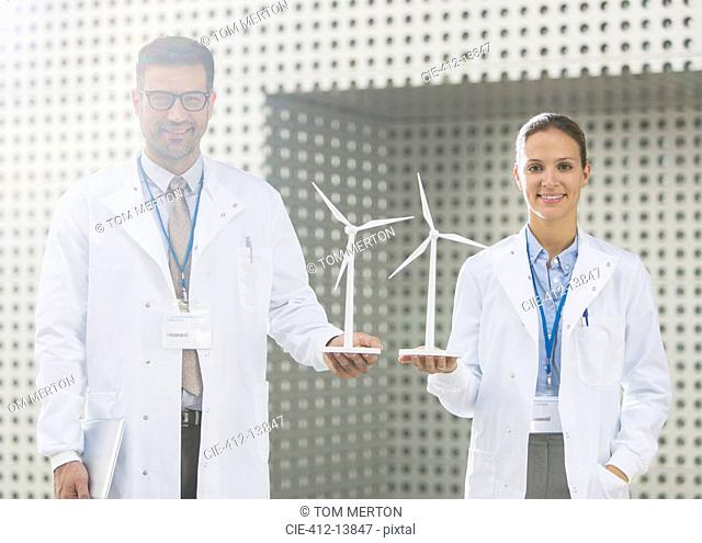 Portrait of scientists holding wind turbine models