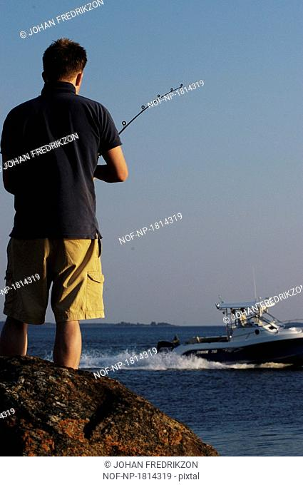 Rear view of a man fishing and boat in background