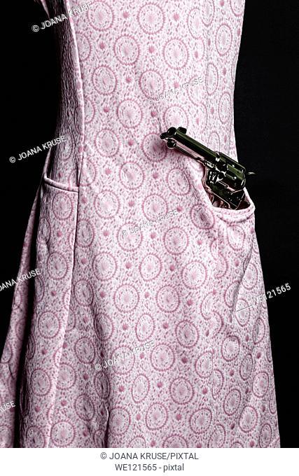 a gun in a pocket of a pink dress