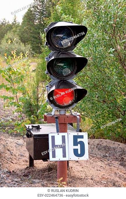 Traffic light shows red signal on railway. Railway station