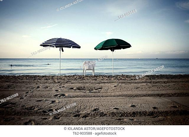 A chair and two umbrellas on the beach  Mediterranean Sea coast  Black and White
