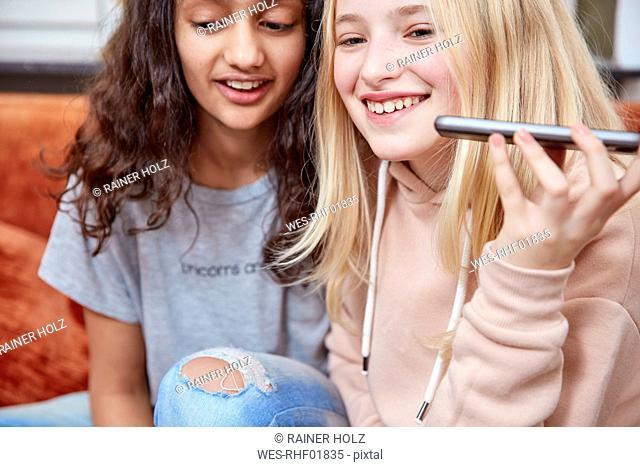 Two happy girls using smartphone