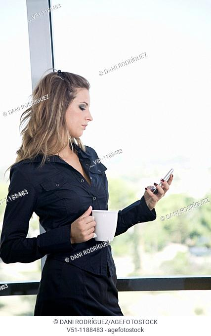 Portrait of a businesswoman with mobile and a cup of coffee