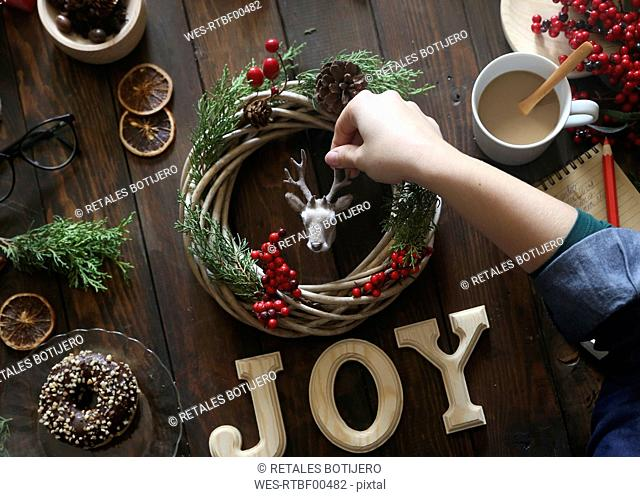 Woman's hand decorating Christmas wreath on wooden table
