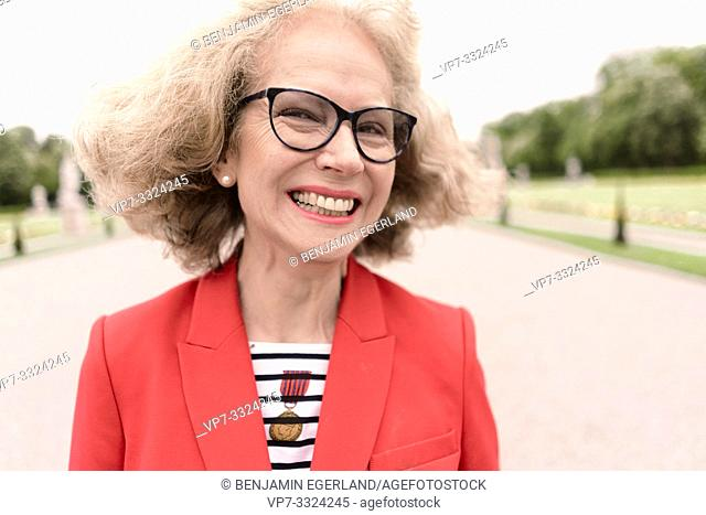 lively senior woman (67 years old) in park, in Nymphenburg, Munich, Germany