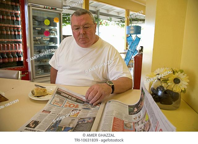 Man Reading Newspaper At Cafeteria Table Adelaide Australia