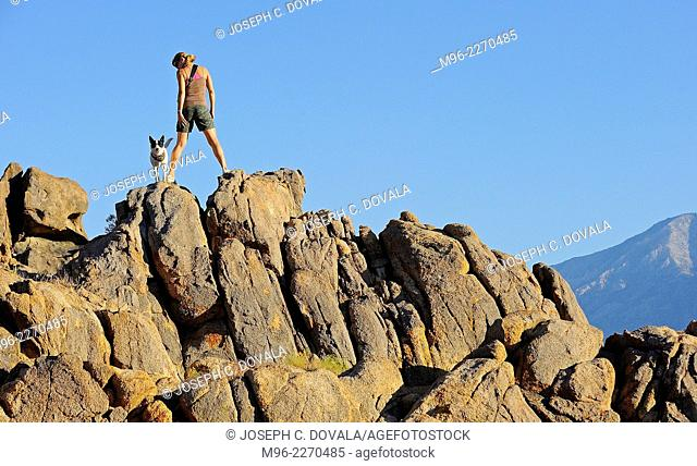 Woman climbing rocks with dog, Alabama Hills, California, USA