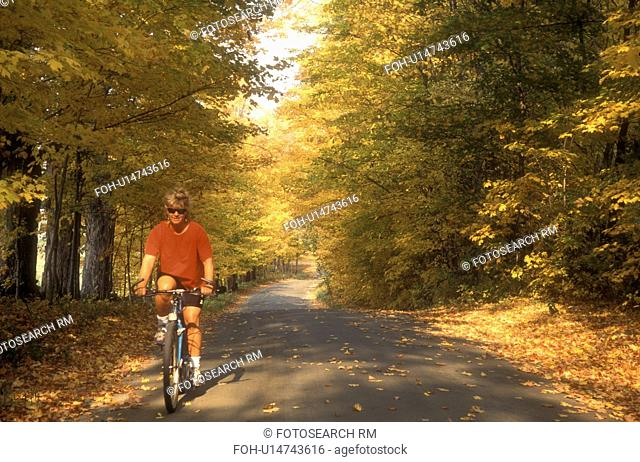biking, woman, country road, fall, East Montpelier, VT, Vermont, Woman biking on a country road surrounded by colorful fall foliage in East Montpelier in the...
