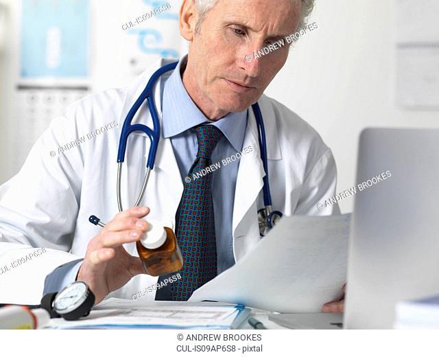 Doctor checking medical notes before prescribing drugs