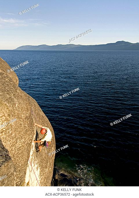 A male rock climber ascends a route at Stillwater bluffs near Powell river on the upper Sunshine coast, Vacouver coast and mountain range, British Columbia