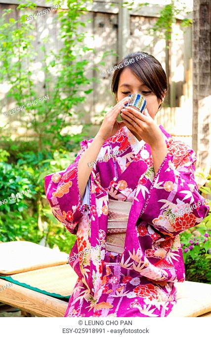 Woman with kimono dress and drink of the tea in tea house