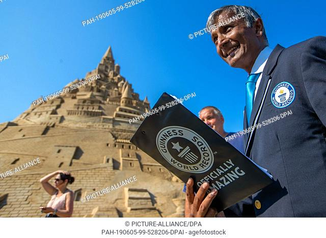 05 June 2019, Mecklenburg-Western Pomerania, Binz: The record judge Pravin Patel stands in front of a new world record sand castle at the Sand Sculpture...