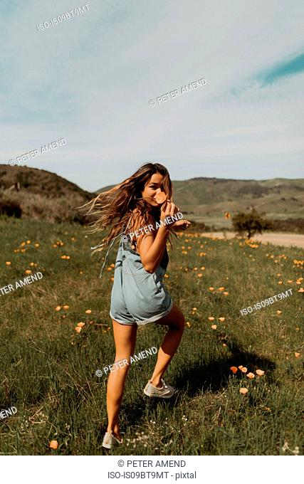 Young woman running in field of wildflowers, portrait, Jalama, California, USA