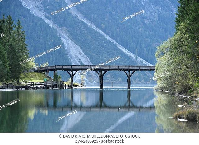 Landscape of a bridge over a small part of a clear lake (Plansee) in autumn in Tirol, Austria