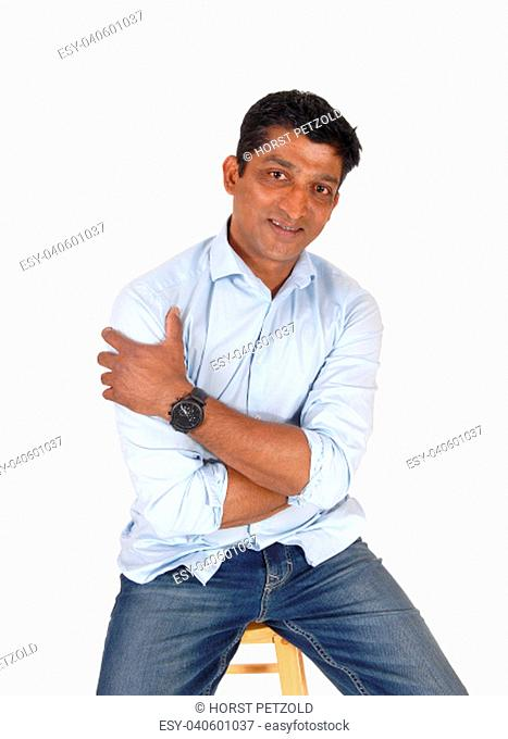 A handsome middle age East Indian man sitting on a bar chair in.jeans and a blue shirt, isolated for white background