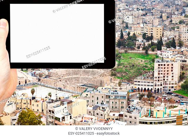 travel concept - tourist photograph ancient Roman theater in Amman city, Jordan on tablet pc with cut out screen with blank place for advertising logo