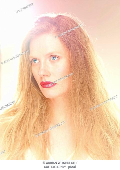 Portrait of a beautiful woman in light, looking away
