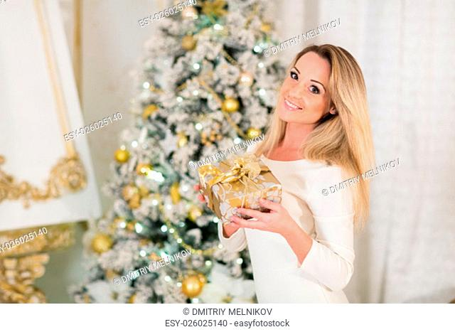 Young happy beautiful woman with gift box stands near Christmas tree in the room of the house. Merry Christmas and New Year