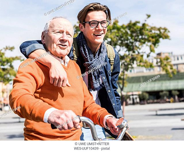Senior man with adult grandson in the city on the move