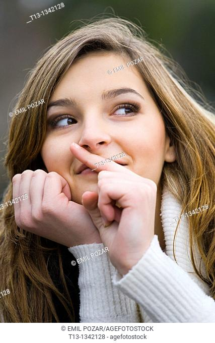 Young woman is mimicking 'silence' with a finger