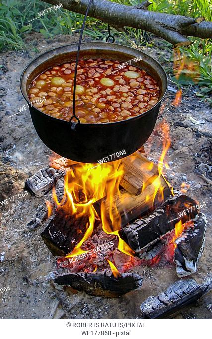 Cooking soup in cast iron boiler on burning campfire. Pot with soup over the open fire outdoors. Tourism in Latvia. Soup cooking on the fire outdoor for camping...