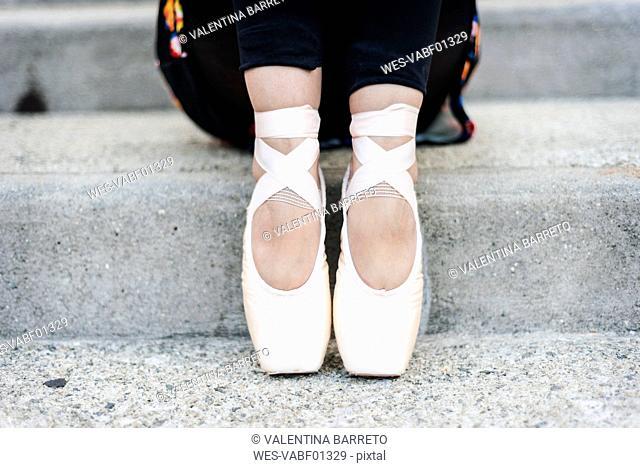 Feet of ballet dancer sitting on steps