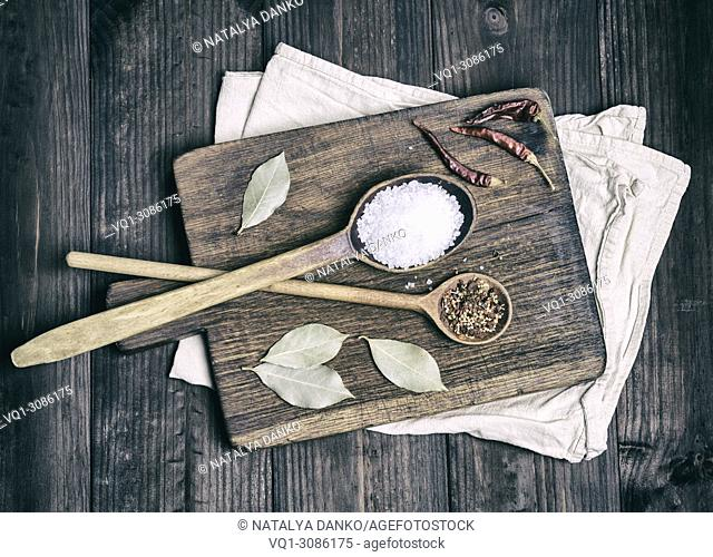 two wooden spoons with spices and white salt on a brown cutting board, top view