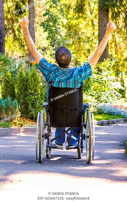 young man in wheelchair with wide opened arms enjoying his life