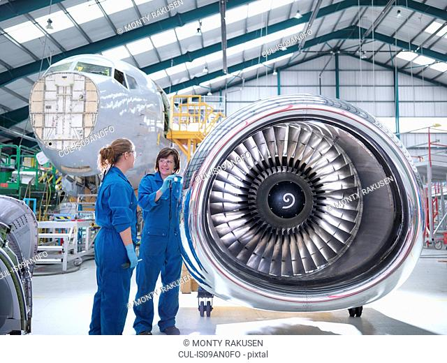 Female engineers working on engine in aircraft maintenance factory