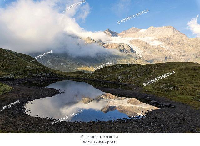 Piz Arlas, Cambrena, Caral reflected in water, Bernina Pass, Poschiavo Valley, Engadine, Canton of Graubunden, Switzerland, Europe