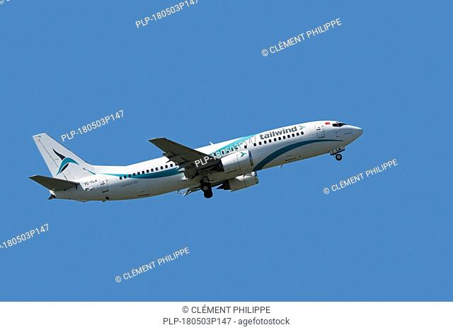 Boeing 737-4Q8, medium-range, narrow-body jet airliner from Tailwind Airlines, Turkish charter airline in flight against blue sky
