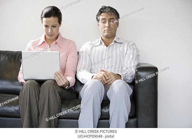 Man spying on woman's laptop